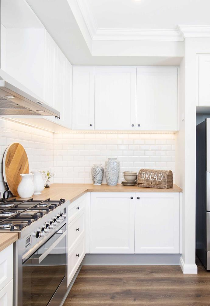 "In the kitchen, shaker style cabinetry with minimalist cabinet pulls are paired with white subway tiles for a classic [country-inspired kitchen](https://www.homestolove.com.au/country-kitchen-design-ideas-13266|target=""_blank""). Clever [task lighting](https://www.homestolove.com.au/task-lighting-ideas-20256