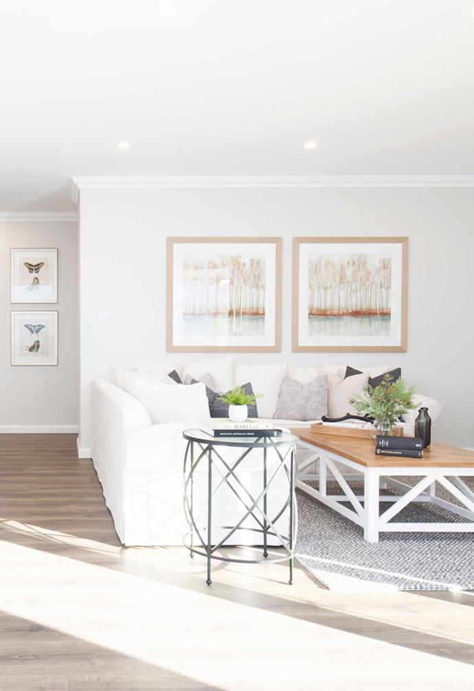 "The living area features classic Hamptons-inspired furniture including a white linen sofa, and timber [coffee table](https://www.homestolove.com.au/10-of-the-best-coffee-tables-13248|target=""_blank"")."