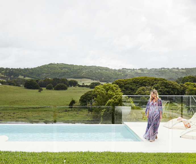 """An infinity swimming pool surrounded by Fibonacci Stone pavers connects the entertaining wing to the rolling hills and blue skies beyond. """"Most days start (and end) with a dive into the pool,"""" Sally says.  The towel on the sunlounge is from Tigmi Trading."""