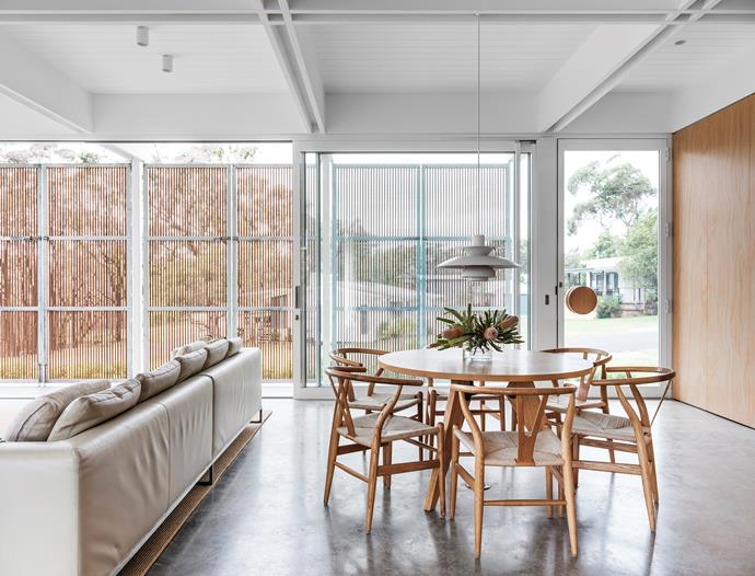A Louis Poulsen 'PH5' pendant light from Finnish Design Shop makes a striking statement over the dining table. Wishbone chairs, Cult. B&B Italia sofa, Space. Burnished-concrete flooring (throughout).