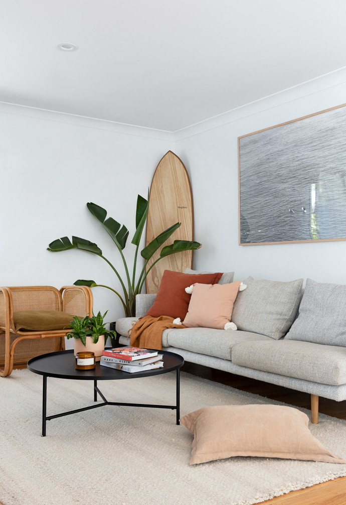 "A photo Britt captured of surfers at nearby Cabarita Beach and had professionally framed is a focal point here, above a welcoming Jardan 'Nook' sofa. The casual surf theme is echoed with a timber Hughies Boards belly board, and layers of texture were introduced with rattan chairs from Worn and Sea Tribe cushions. A generous Pampa 'Monte' rug anchors a Temple & Webster coffee table. ""In summer we're mostly outside, but this is a nice, cosy area to retreat to,"" says Britt."