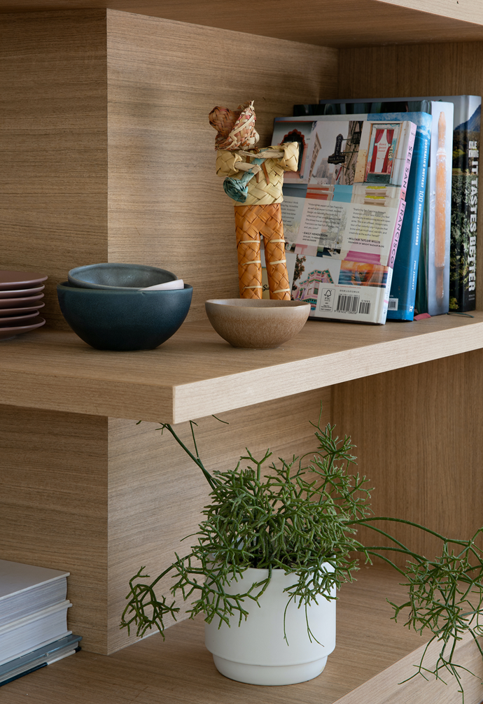 In the kitchen, Laminex 'Classic Oak' cabinetry niches are filled with cookbooks and travel mementos.
