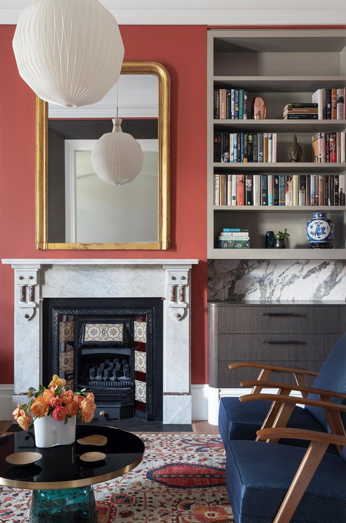 The clients' antique brass mirror hangs above the fireplace against a wall painted in Resene 'Forbidden'. Joinery in Eveneer 'Grigio' from Elton Group with a honed Concordia marble insert and Buster + Punch pulls from Living Edge. Vintage chairs reupholstered by Atelier Furniture in Zimmer + Rohde fabric from Unique Fabrics. ClassiCon 'Bell' coffee table from Anibou. Farahan fine wool rug from Robyn Cosgrove.