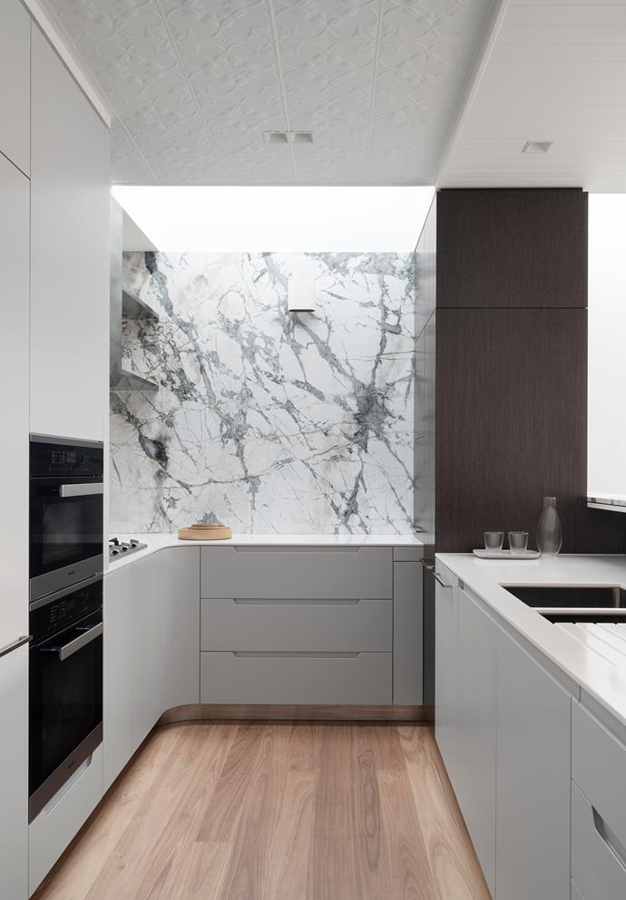 The pressed-metal ceiling coffer was suggested by the clients and creates a nod to the home's heritage in the otherwise ultra-modern kitchen outfitted with a Miele steam cooker and oven. Blackbutt flooring from Austral Timbers. Corian 'Glacier