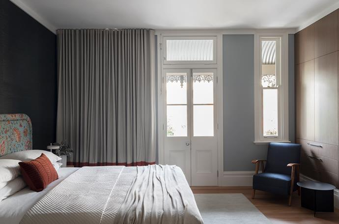 The master bedroom is wrapped in the soft tones of a sisal wallpaper from South Pacific Fabrics, walls in Porter's Paints 'Newport Blue' eggshell finish, curtains with a contrasting band in fabric from Unique Fabrics and wardrobes by Space Joinery in Eveneer 'Xilo Sand'. Custom bedhead in fabric from Boyac, Ralph Lauren bedcover from David Jones and Bemboka throw. Agra rug in Pearl from Armadillo and Hay 'Slit' side table from Cult.