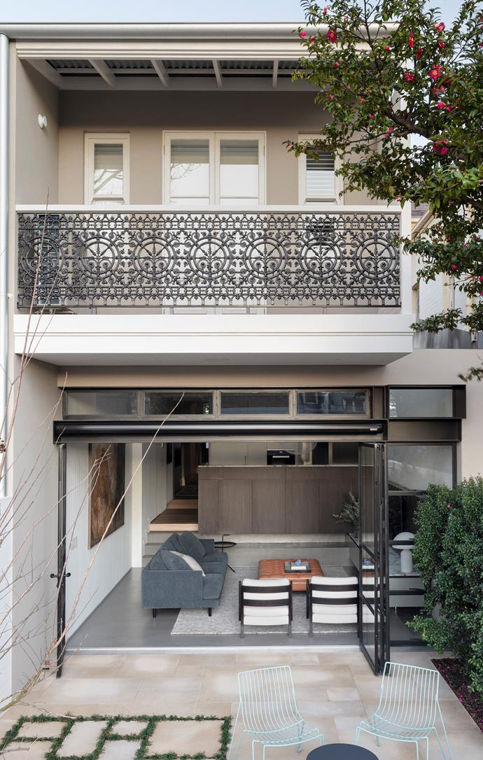 Lacework panels from Central Foundry. Custom steel-frame doors with an Olivari 'Uovo' lever open to the rear courtyard with custom metalwork by All Metal Projects framing the window to the right and an Aluxor 'Discus' folding-arm awning providing shade above. 'Tio' outdoor chairs from Spence & Lyda.