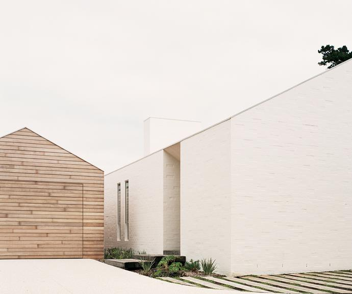 """""""The brief was for external materials to be hardwearing and robust to withstand the local environment,"""" says architect Dominic Pandolfini of the shiplap timber cladding, bagged brickwork in Porter's Paints 'Milk' stone paint and Colorbond 'Ultra' steel roofing in Shale Grey."""