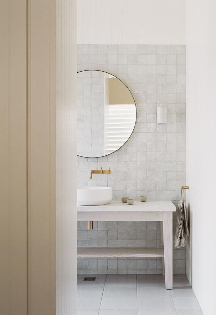 These ceramic wall tiles from Tiles of Ezra subtly reference Moroccan style while the Brodware 'Yokato' bathroom fixtures in organic Brushed Brass will patina and add character over time. The Zen basin is by Apaiser, the sconce is from Anchor Ceramics, and the brass-frame mirror and stone-top vanity are both custom pieces.