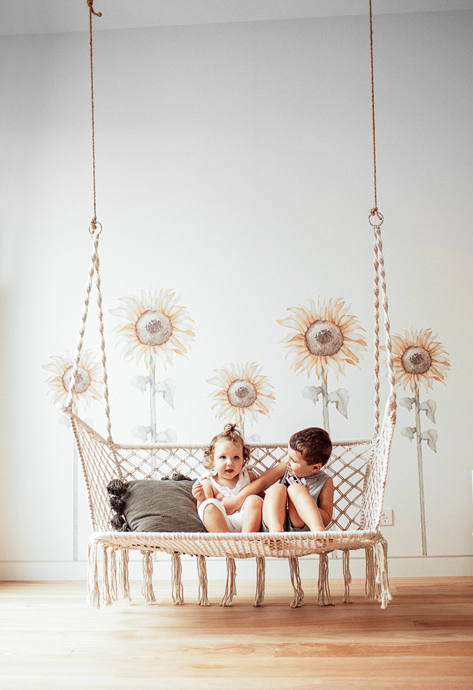 In the polished yet playful rumpus room is a macrame hanging chair from Temple & Webster. Behind Edison and Mabel are sunflower wall stickers from Little Rae Prints.