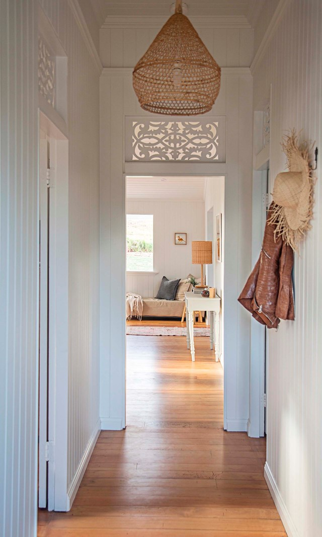 "Old and new meld together in the entrance hall of this [relocated Queenslander](https://www.homestolove.com.au/relocated-queenslander-renovation-22211|target=""_blank""). The home's original latticework and pine floors were lovingly restored by the owners while contemporary accents, like the rattan light shade reference the home's new coastal location."