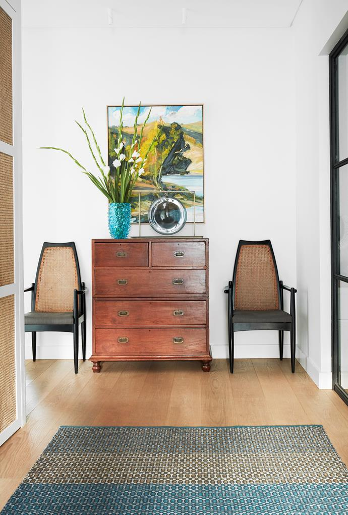 A thoughtfully decorated space at the end of the hallway comprises a vintage chest of drawers and a pair of cane-backed chairs from The Vault Sydney. Artwork by Robert Malherbe. Kasthall rug from Space. Murano vase from Conley & Co.