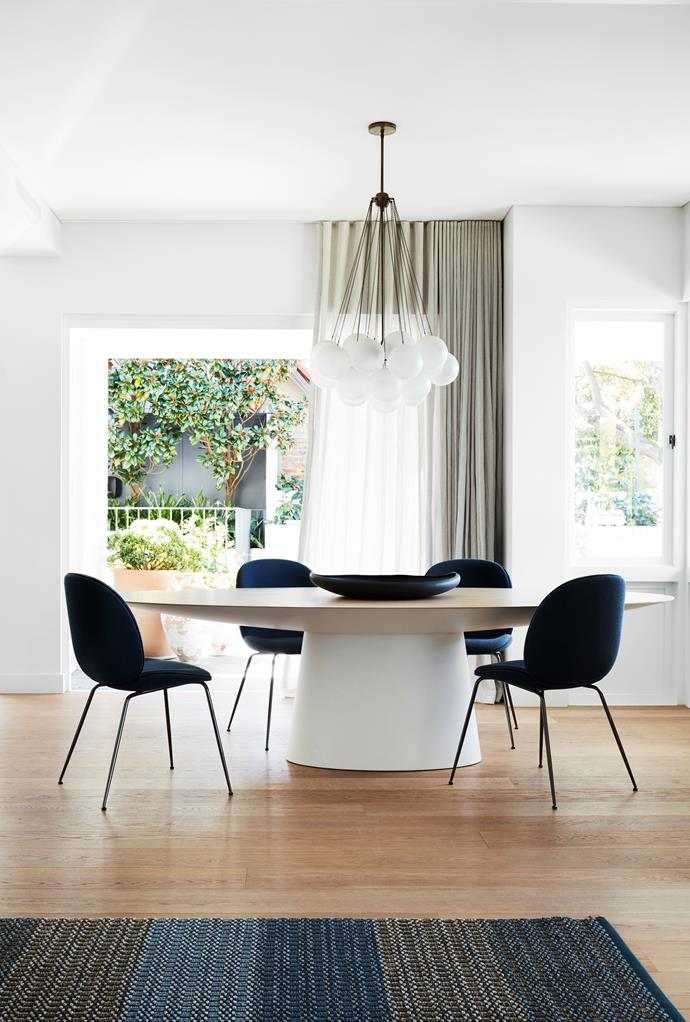 Emmemobili 'UFO' dining table is attended by Gubi 'Beetle' chairs from Cult upholstered in Kvadrat 'Coda'. Kasthall rug from Space. Apparatus 'Cloud' chandelier from Criteria.