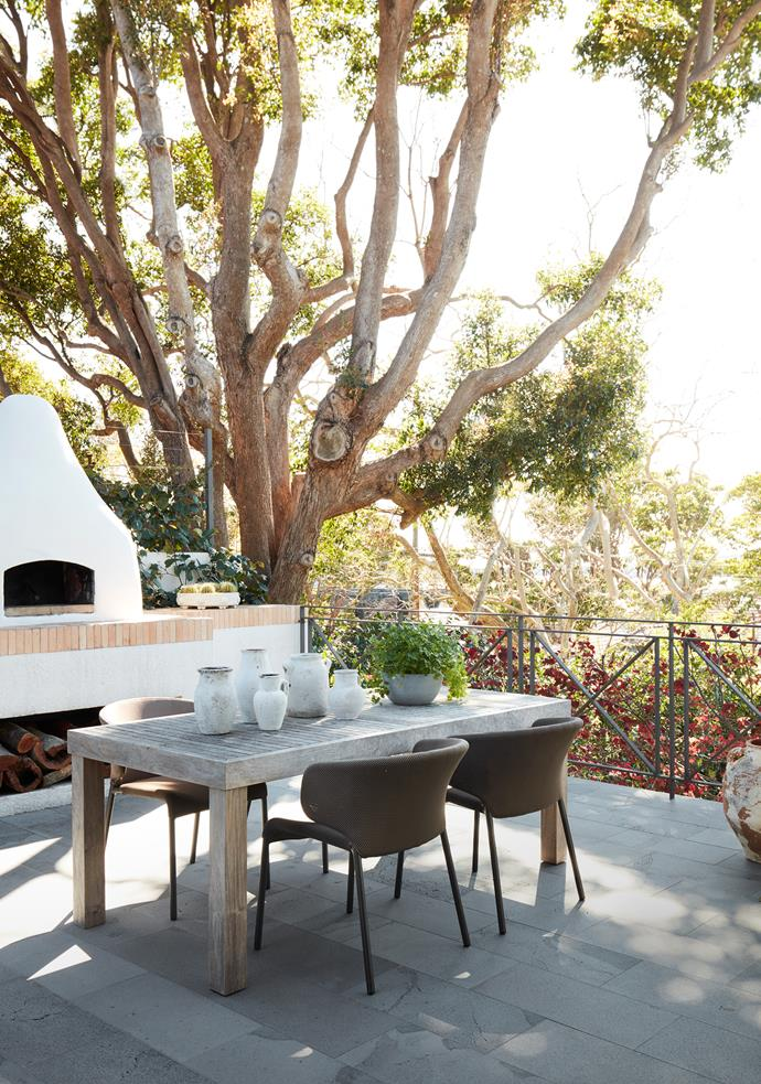 One of the outdoor living areas is located near the pizza oven and enjoys filtered water views. Table from Robert Plumb with Roda outdoor chairs from Domo. Pots and plants from Garden Life.