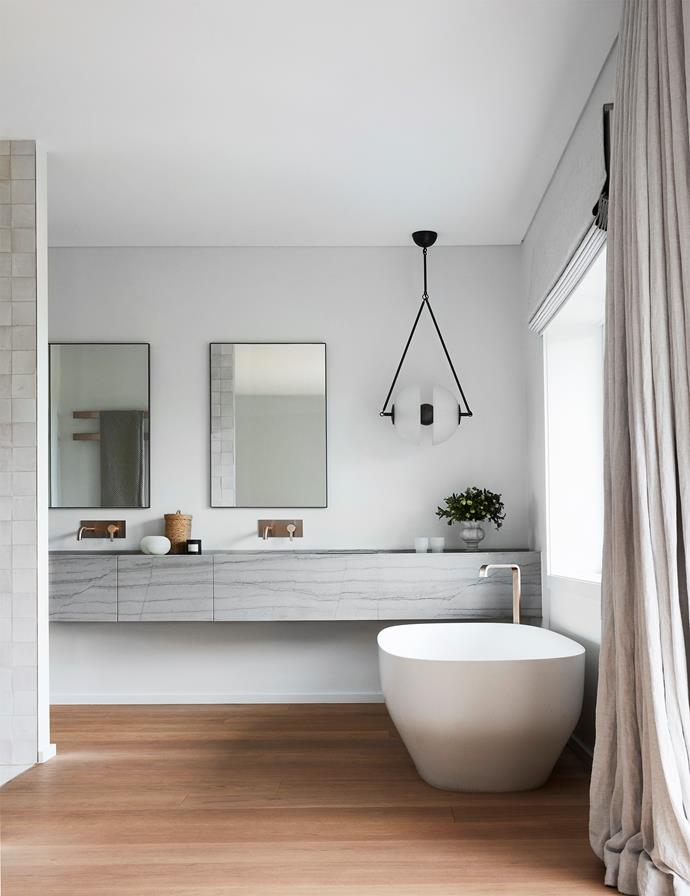 The ensuite bathroom has stone from SNB Stone and custom mirrors by Hugh-Jones Mackintosh. Apparatus pendant light from Criteria. Curtains by Simple Studio.