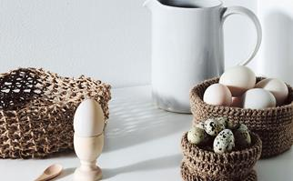 Crocheted string baskets filled with eggs on a white table next to a milk jug