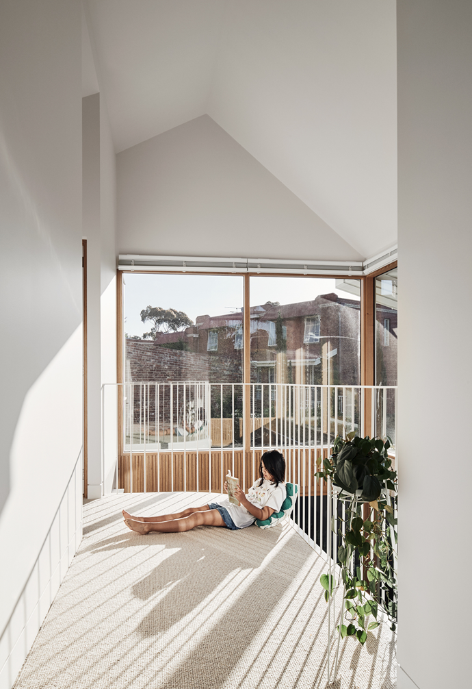 """A mezzanine balcony offers a sunny spot for repose on the first floor's Cavalier Bremworth 'Levante' carpet. As one of the homeowners reflects, """"I like sitting on the inside balcony with the sun coming through and looking out on the roof garden and all the large trees in Royal Park"""". The powdercoated railing is custom and the plant stand is Supply & Demand. The cushion is by architecture firm Timmins + Whyte."""