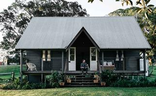 Dark grey cottage with white front doors and a man sitting on the front steps