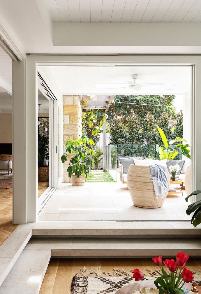 Custom sliding doors by Planbuilt open up to draw summer inside. The same Aren Bianco limestone from Onsite Supply & Design used for the living-room steps continues to the paving, to further enhance the flow.
