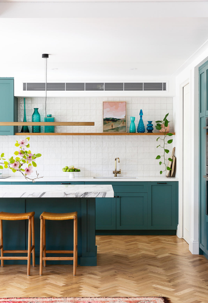 """""""I wanted a green kitchen, and our amazing painter Matt Hills was able to mix the perfect dirty teal colour for me,"""" says Lou. The profile of the joinery, designed by interior designer Emma and installed by Planbuilt, references a traditional English kitchen – but the modern 'Capital' brass light from Rakumba and leather barstools from Fenton & Fenton freshen the look, as do a glazed Spanish tile splashback from Tiles By Kate and a benchtop made of honed Arasbescato marble. Blue vases and a pretty landscape artwork (Rolling Hills by Rachel Stevens) add character to a recycled blackbutt shelf. In the adjacent sunken living room, a must-have in the layout, eyes focus on Olivier Rasir's abstract piece Omnia."""
