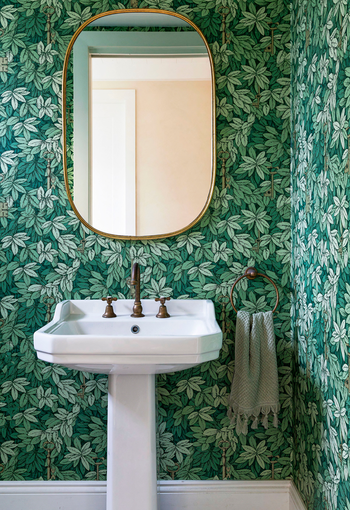 """'Chiavi Segrete' wallpaper by Fornasetti is a fitting backdrop for a pedestal sink and aged brass 'Icon' hardware from Astra Walker. """"This is the one place where you can go for it,"""" says Lou, a big fan of using wallpaper in the powder room."""