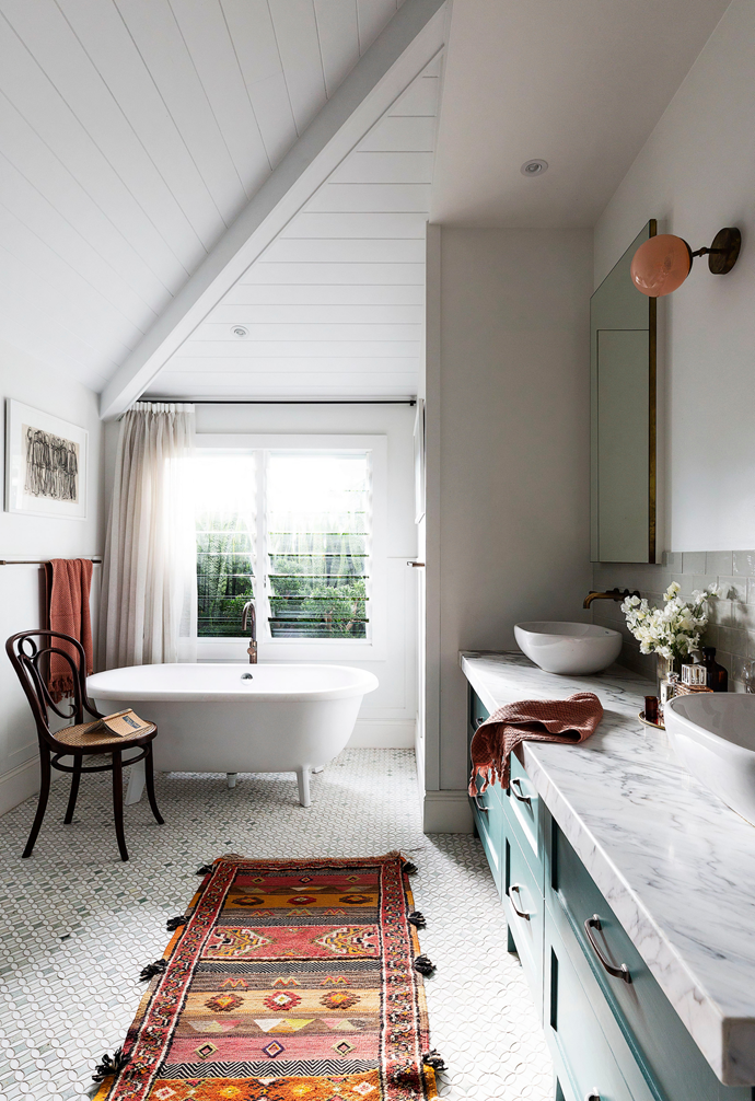 """""""I love the sense of space in the master en-suite. It's quite indulgent , like a retreat."""" ~ Lou. Calmness washes over the ensuite, where an Agape 'Ottocento' cast iron bath from Artedomus perches on marble mosaics from Marable. The look is streamlined splendour. """"I didn't want to see any electrical outlets or cords,"""" says Lou of what is hidden by the vanity drawers."""