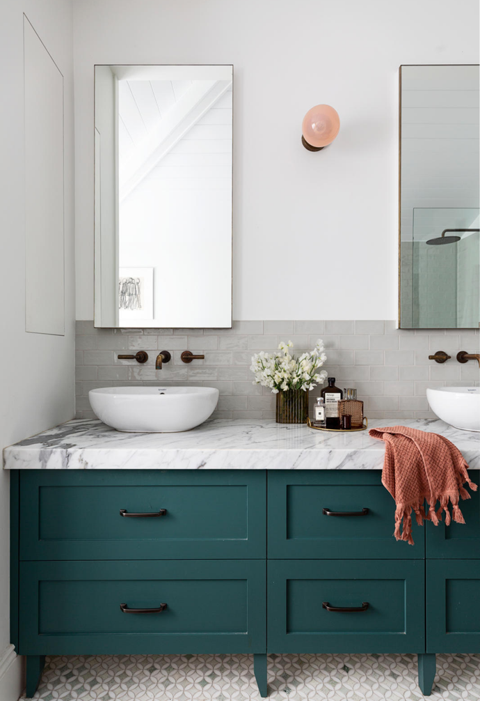 Emma designed the vanity using a custom teal cabinet colour and an Arabescato marble benchtop. A runner from Morocco, a 'Line' wall sconce by Douglas & Bec and dusty pink Temple & Webster towels complete the soothing palette. An artwork Kev created back when he was at art college overlooks the tub.