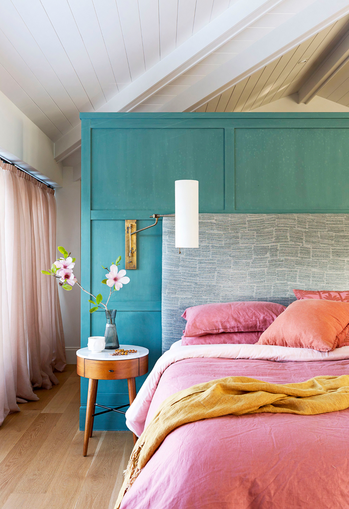 """Lou and Kev's bedroom suite takes understated luxury to new heights. The joinery behind the bed was finished in a custom Porter's Paints colour with a waxed effect and cleverly hides a walk-in wardrobe. """"The bed is an island in a big, voluminous space, which makes it all about the ceiling height,"""" says interior designer Emma. The bedhead is upholstered in Rubelli 'Reloaded' jacquard from South Pacific Fabrics, with linen bedding from Bed Threads, and 'Penelope' bedsides from West Elm match the wall lights from Circa Lighting."""