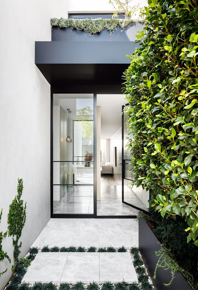 A verdant and bold entryway greets guests. The steel-frame doors are simple but impactful.