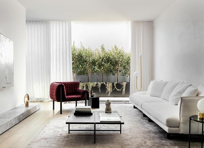 The light-filled living area features modern furnishings, pared-back detailing.