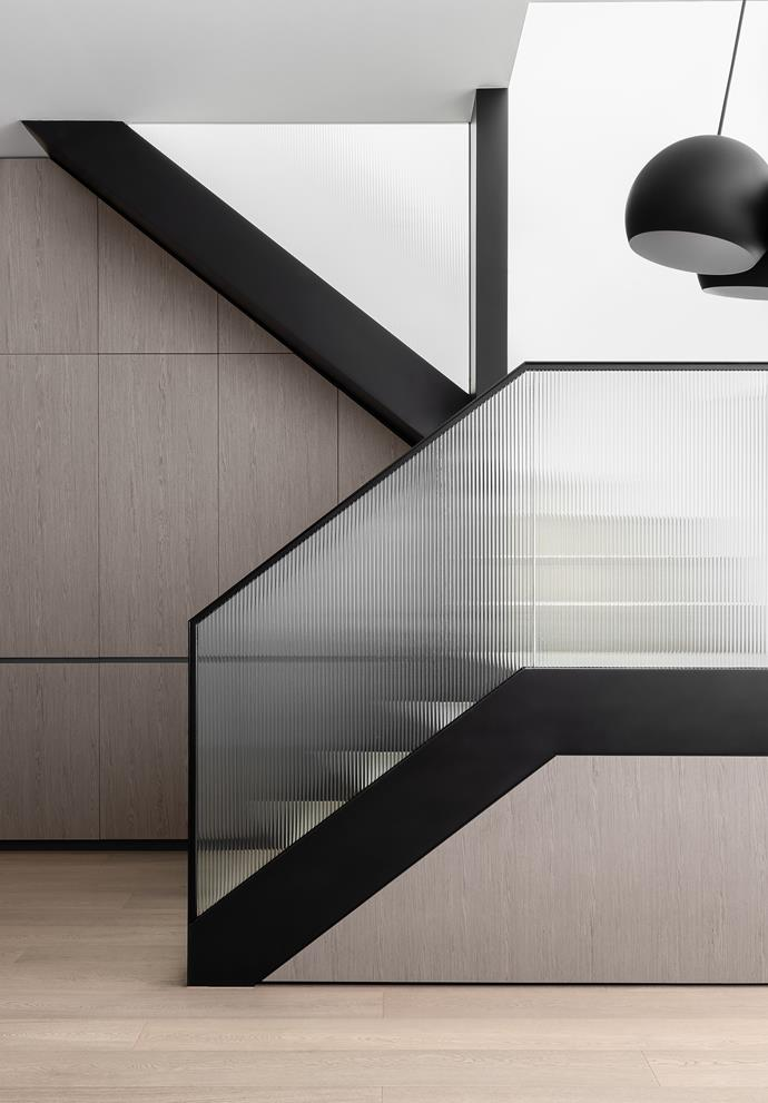 A fluted glass balustrade makes an elegant statement on the the stairway.