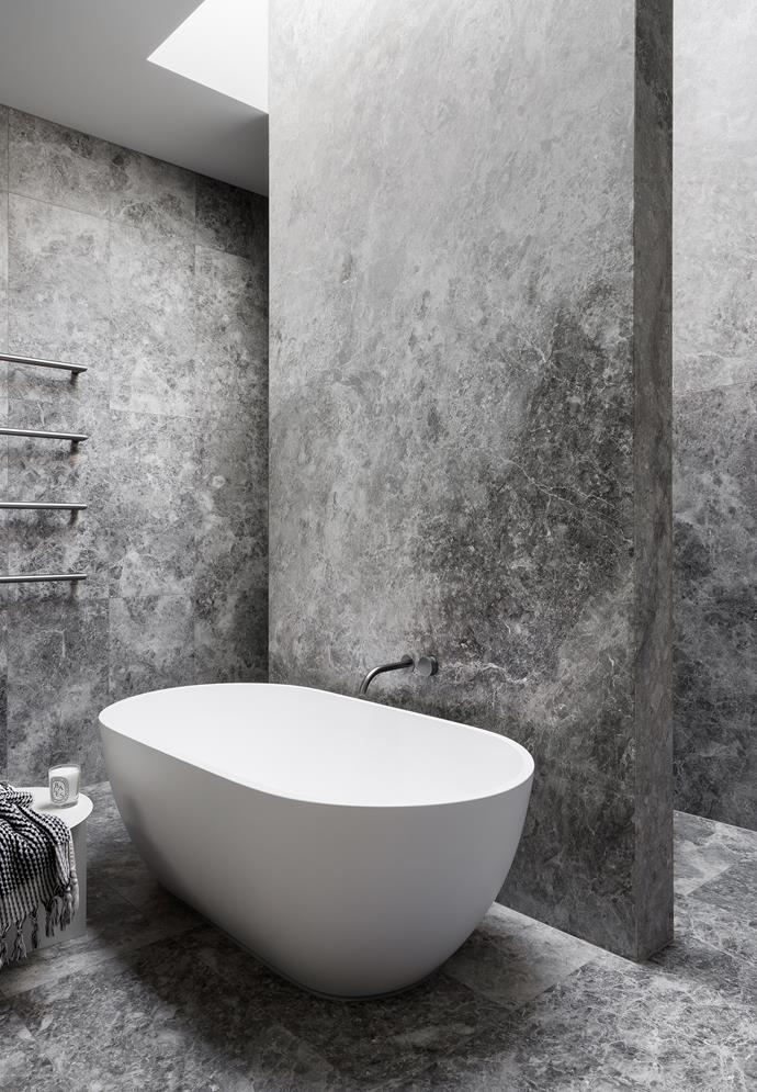 The marble-clad ensuite which boasts an indulgent freestanding bath illuminated by a skylight.