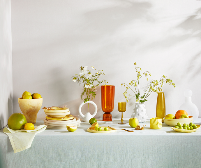 Linen flat sheet in Moonlight (used as tablecloth), $199 for queen, Sage and Clare. Luisa Beccaria striped linen napkin in Pale Green, $577 for set of 2 including 2 placemats, Matchesfashion. Offering vase in Lemon, $280 for large, Dinosaur Designs. Shore 5-piece flatware set in Bronze, $135.39, Casa Shop. Doughnut bowls, $110 each, side plates, $90 each, and dinner plates, $130 each, Softedge Studio. Femme hoop vase in Speckled White, $120, Eun Ceramics. Hay 'Bottoms Up' vase in Amber, $150, Amara. R+D.Lab 'Luisa' wine goblet, $187 for set of 2, and glass carafe in Green, $191, Matchesfashion. Carron Mademoiselle vase, $420, and brass snail, $24.95, The Lost + Found Department. Cup for Fingers cup in Lemon, $65, Softedge Studio. Pebble bowls in Citrus, $72 each, Mud Australia. Seed plate in Lemon, $95, Dinosaur Designs. Stella decanter in Opalescent, $264, Casa Shop. Carron Mademoiselle salad bowl, $259, The Lost + Found Department.