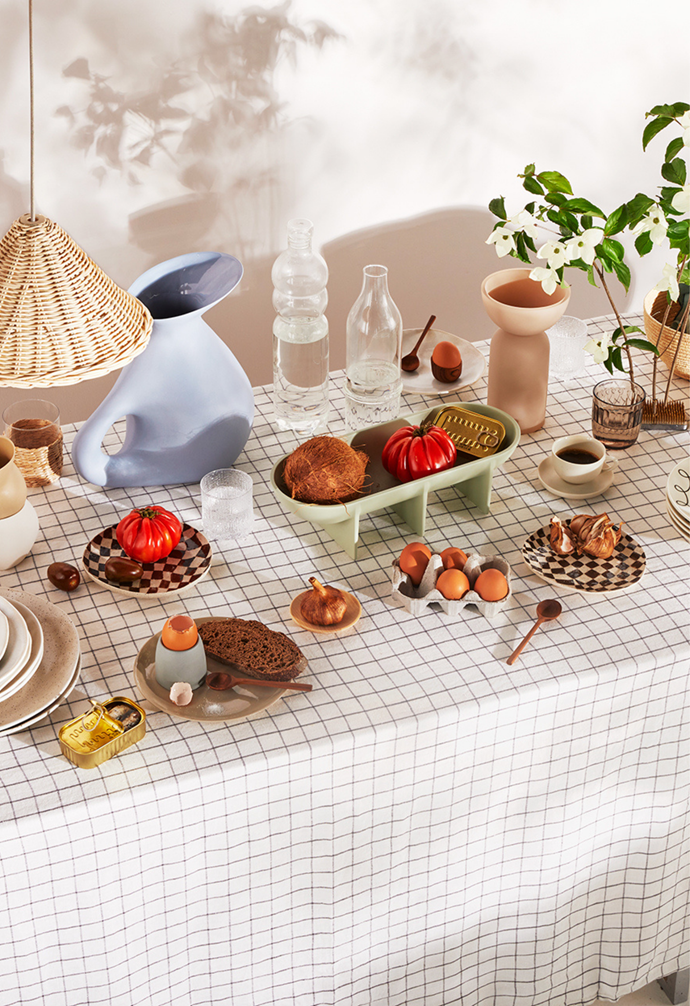 Linen table cloth in Grid, as before. Lulu linen napkins in Sky, $80 for set of 4, Jardan. Birch bowls, $21 each for large, Plyroom. Volumes bowl in Latte, $120, Softedge Studio. Teak mortar and pestle, $49, McMullin & Co. Stoneware share plates, $120 for set of 3, Open Objects Studio. Earth side plates, $24.95 each, and dinner plates, $29.95 each, Robert Gordon. Kristina Dam 'Dual' vase in Cream, $179 for medium, HK Edit. Glass tumbler with rattan sleeve, $15 for set of 4, Target. Cup with Curves cups in Latte and White, Ewer jug in Cornflower and Chequerboard side plates in Coco, all as before. Ultima Thule 'Old Fashion' glasses, $89.95 for set of 2, Iittala. Bread plate in Sand, $39, and egg cup in Ash, $44, Mud Australia. Teak spoons, $9 each, McMullin & Co. Birch bowl, $15 for small, Plyroom. Fort Standard 'Standing' bowl in Sage, as before. Seletti bottle and Ichendorf Milano 'Transit' tall bottle. Teak egg cup, $18 for set of 2, McMullin & Co. Kristina Dam 'Dual' vase in Sand, as before. Espresso cup and saucer in Milk, $69, Mud Australia. Raami tumbler in Linen, $34.95 for set of 2, Iittala. Muse bowls, $36 each, Chloe Dimopoulos. Teak salad servers, $29, McMullin & Co. Raffia bowl, $89, Clo Studios. **ABOVE TABLE** Rattan lamp shades, $145 each, Water Tiger. **ON WALL** Wash&Wear low sheen acrylic paint in Japanese Poet.