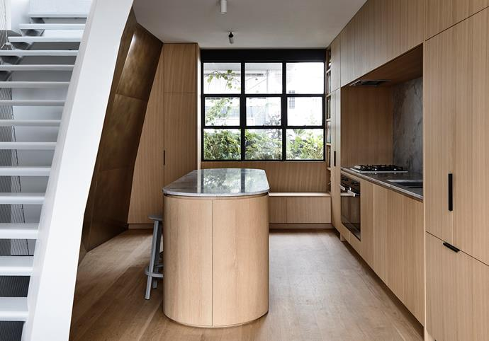 A curved end of the kitchen island lends softness to the space and draws attention to an angled wall delineating the central stairway. Super White Dolomite from CDK Stone has been used for the benchtop and island to offset the all-timber joinery. Hay 'Revolver' stools from Cult.