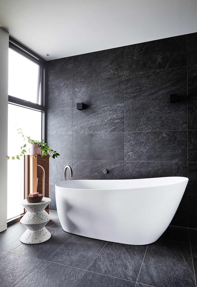 **Ensuite** The striking white freestanding bathtub becomes a stunning visual feature contrasting dramatically with the dark tiles.