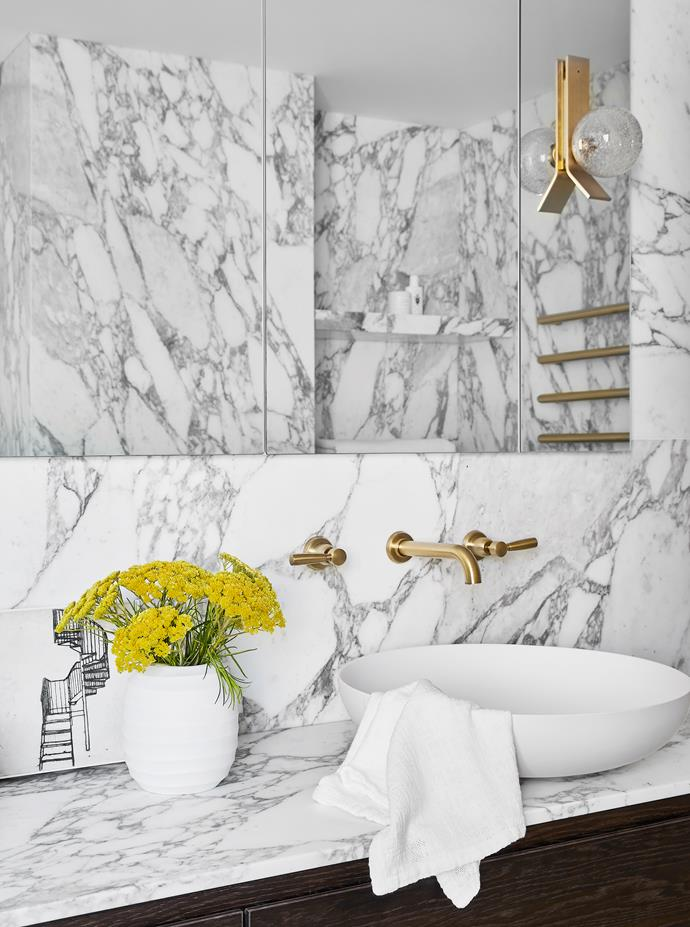 Arabescato marble from Granite & Marble Works clads the walls in the master ensuite. Basin, towel rails and Brodware tapware, all from Candana. Articolo 'Fizi' wall light from Est Lighting. Bec Stevens artwork from Planet. Guaxs vase from Conley & Co. Hand towel from Ondene.