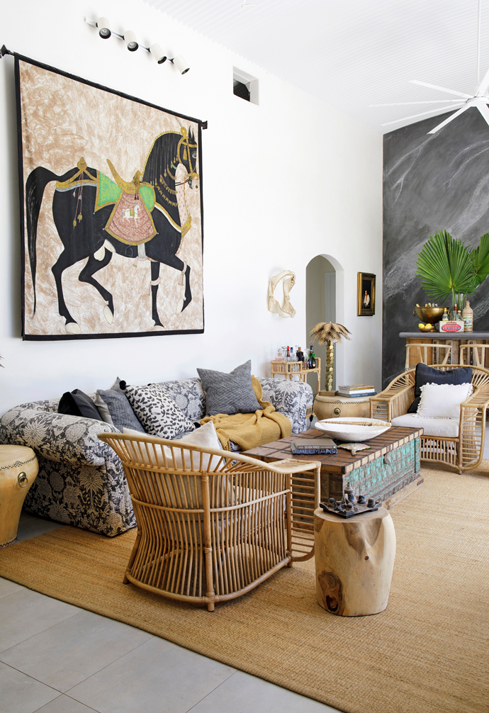"""Naturally hued pieces from CLO Studios including cane chairs, a rug and timber bar stools increase the warmth in the sunroom, while on the wall, the fabric hanging has taken pride of place for decades. """"It was commissioned by the Maharishi of Udaipur in Rajasthan to celebrate the birth of his first daughter,"""" says Chris. """"I found it in an Indian store."""" Beside it, flanking the doorway are """"shark jaws of a white pointer caught in Queensland around 20 years ago""""."""