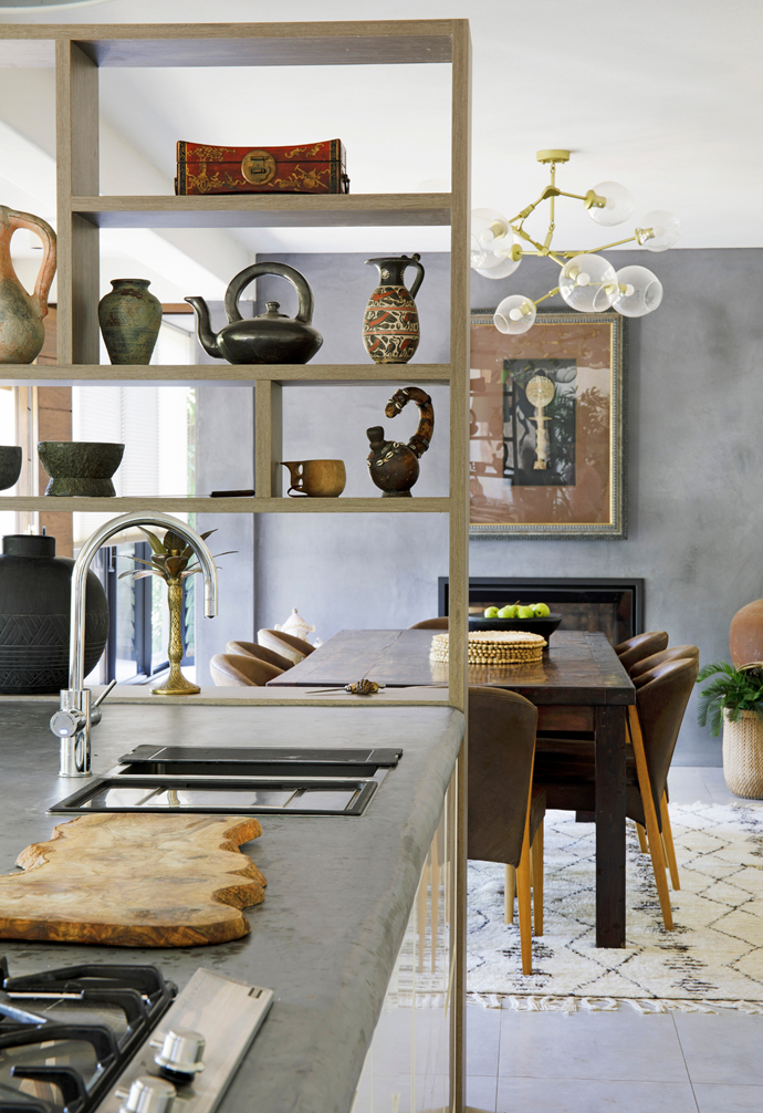 """In one of the project's most significant changes, a wall dividing the kitchen and dining area was demolished and replaced with shelving by Modern Nova, for a more open feel. """"Now there's a greater sense of connection to the kitchen, which really is the hub of the home where we love to congregate with friends,"""" says Chris. Shelves are adorned with treasures from the couple's travels, including pots from Pompeii, a Vietnamese smoking pipe and an ornate Chinese box. The framed west African Akua'ba doll that sits above the fireplace in the dining area was found locally at the renowned Eumundi Markets."""