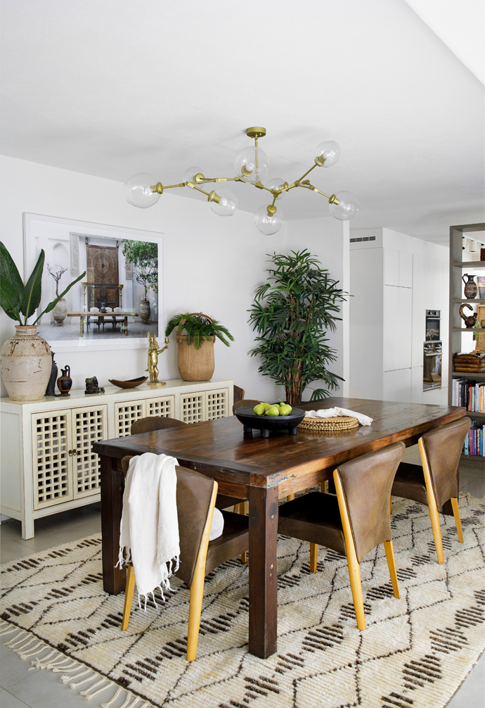 A table from Eclectic Style and chairs Chris and Bob have had for years were refreshed with an Armadillo rug and crowned with a 'Branching Bubble' chandelier from Mica Lighting. The console from CLO Studios is topped with gifts and travel mementos.
