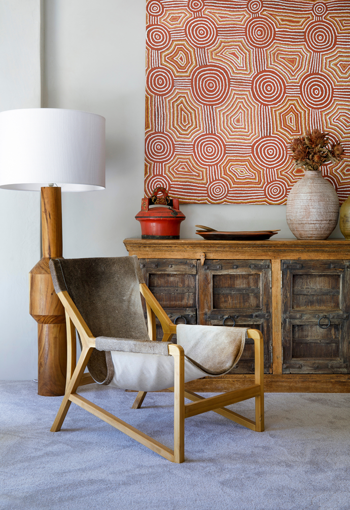 The late Papunya artist John Tjakamarra's untitled artwork overlooks an Eclectic Style buffet with an 'Arbus' floor lamp and 'Dolce' armchair, both from CLO Studios, bringing in textural appeal, as do a Moroccan bowl, also CLO Studios, and a vintage teapot atop a Uniqwa 'Log' coffee table