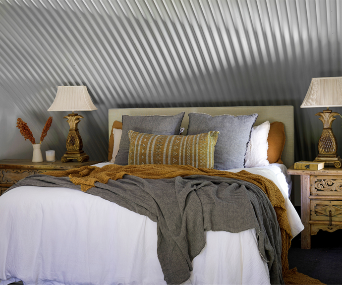 """""""Our bedroom has always been so peaceful and inviting,"""" says Chris of their upper-floor escape. Above the bed, a corrugated ceiling generates a cosy feel, as do a custom upholstered bedhead and relaxed layers of Hale Mercantile Co linen in earthy tones. A carved Moroccan timber bedside table from CLO Studios holds a vintage pineapple lamp Chris has treasured for years."""