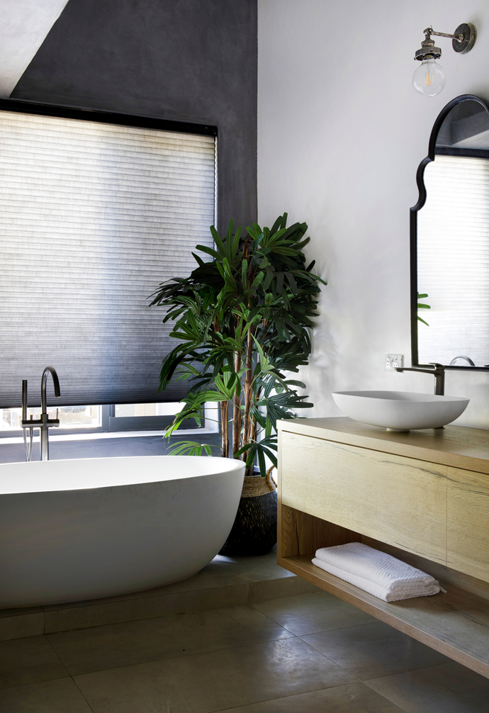 """The centrepiece in the ensuite is a curvaceous Corian [freestanding bath](https://www.homestolove.com.au/freestanding-bath-design-ideas-4520