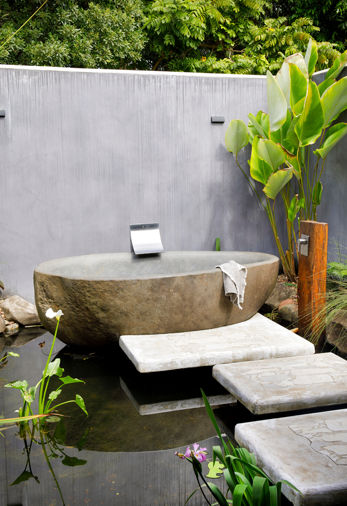 """""""It was Bob's idea to put the bath in a pond, which was genius,"""" says Chris of the solid stone tub and Fienza 'Vinci' waterfall spout from North Coast Plumbing, which is reached via suspended concrete slippers. """"Taking a bath is an incredibly tranquil experience,"""" says Chris. """"At night under the stars, it's just magical."""" For a solid stone bath, try Stonebaths.."""
