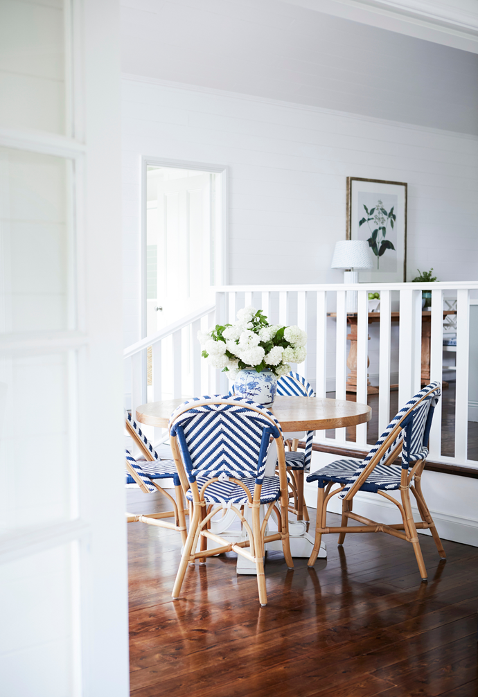 Stepped down from the kitchen, a casual dining spot comprises a round table of Melinda's and a striking, stripy set of four Parisian bistro chairs. The white balustrade adds an interesting detail and zones the living space without blocking it off from the rest of the home. The perfectly placed botanical print by Designer Boys Art is available at Living By Design.