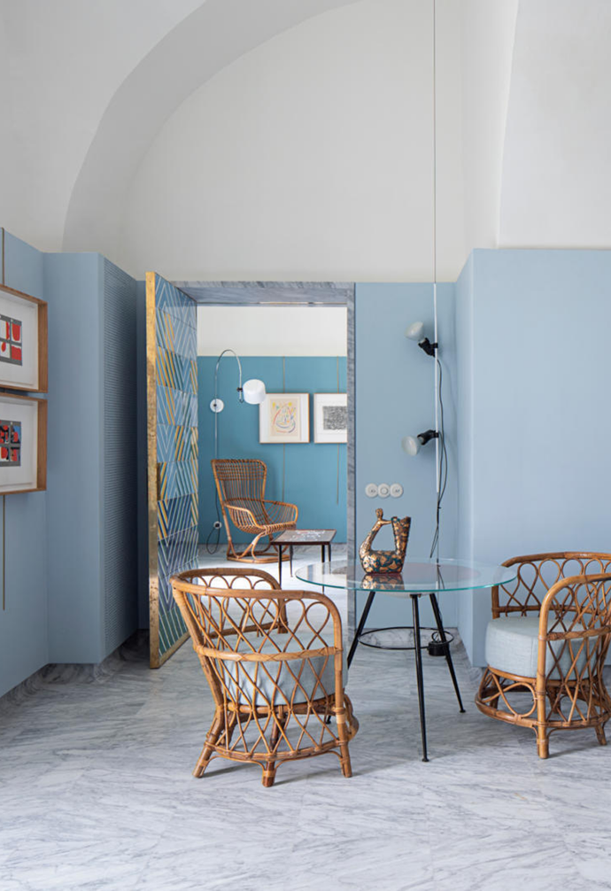 The holiday house's small dining nook consists of an original 1950s glass-topped table from Retro4M with Lio Carminati armchairs from Demosmobilia. The two wall prints are by Alberto Burri. The kitchen is clad in a selection of custom ceramic tiles by Francesco De Maio, which are a celebration of the colours of the natural landscape. Vintage pendants and a Vallauris 'Shell' lamp evoke feelings of yesteryear.