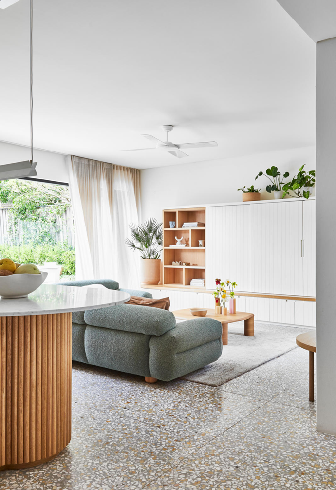 """Custom joinery by HBH Joinery features open shelving where decorative objects can be displayed. """"Panels slide across to conceal the TV, which was an important feature for us,"""" says homeowner Owen Ow. The Valley modular sofa is an ideal gathering spot for his young family."""