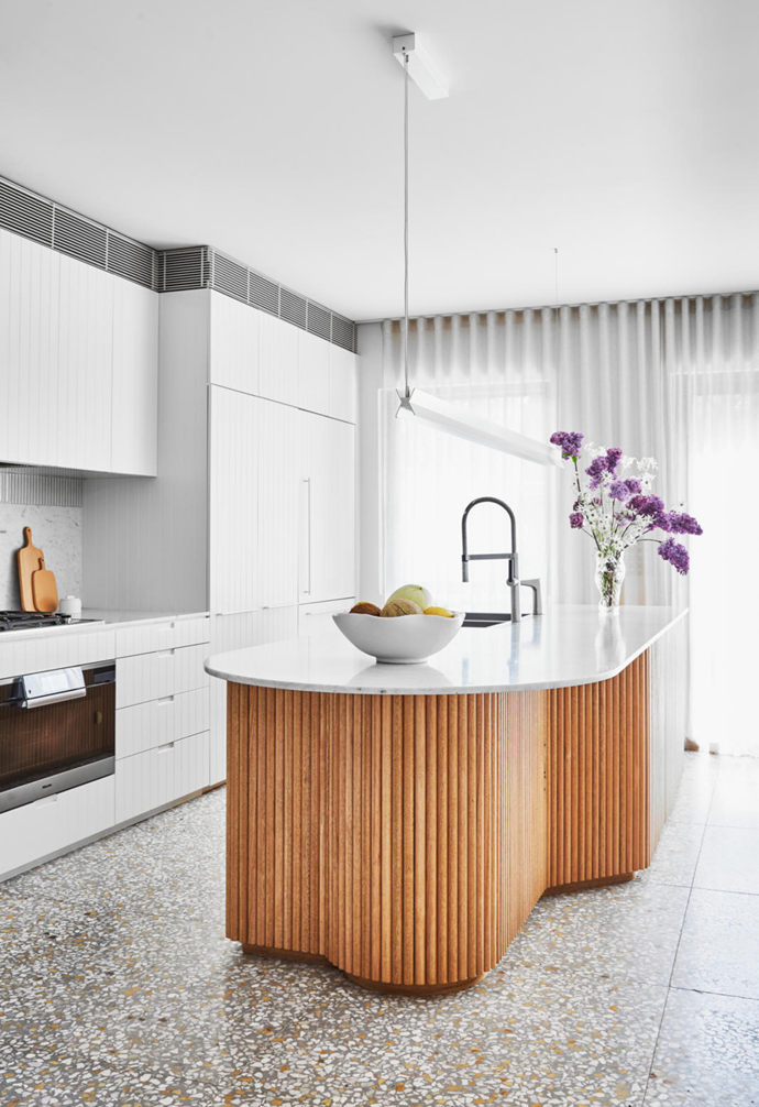A timber dowel and marble-topped kitchen island ties in with the home's other curved features, and has in-built storage to suit the family's needs. A Span pendant from Living Edge hovers above while a Clementine bowl from McMullin & Co holds fresh fruit. Soft silhouettes The curved contours continue in the dining area, from the joinery and shelves to the table, stools and arched entrance. A Hat pendant by Luke Mills is the final rounded flourish.