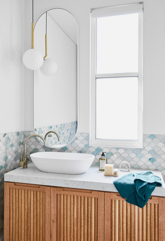 "The couple's bathroom features a Flos 'S1' suspension light from Living Edge and Ming green fishscale tiles. ""They create such a feeling of calm and serenity,"" Elaine says of the tiles."