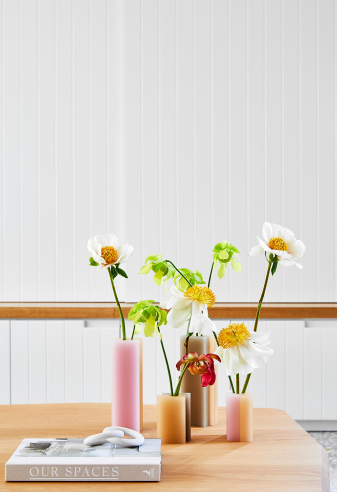 Dean Toepfer vases from Makers' Mrkt and ceramic rings from Atley.Co sit atop a Jardan coffee table in the bright and airy living space.