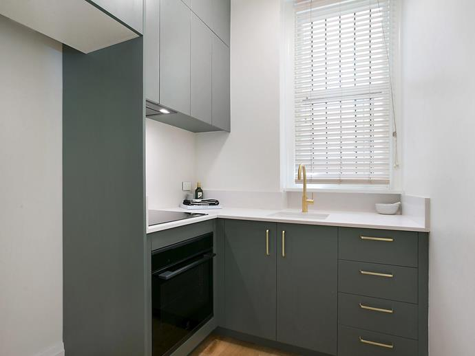 The compact kitchen features sleek cabinetry in an on-trend olive green tone.